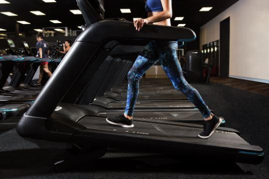 Close up of female in professional gym environment on a Precor TRM 800 Line treadmill walking at high incline
